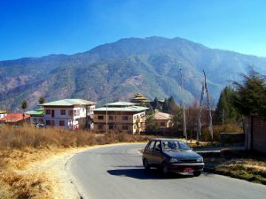 One of the many roads that lead to one of the Best Places To Visit In Thimphu Bhutan, an ancient temple named Changangkha Lhakhang. You can see it in the distance, with its yellow roofs against the green mountains.