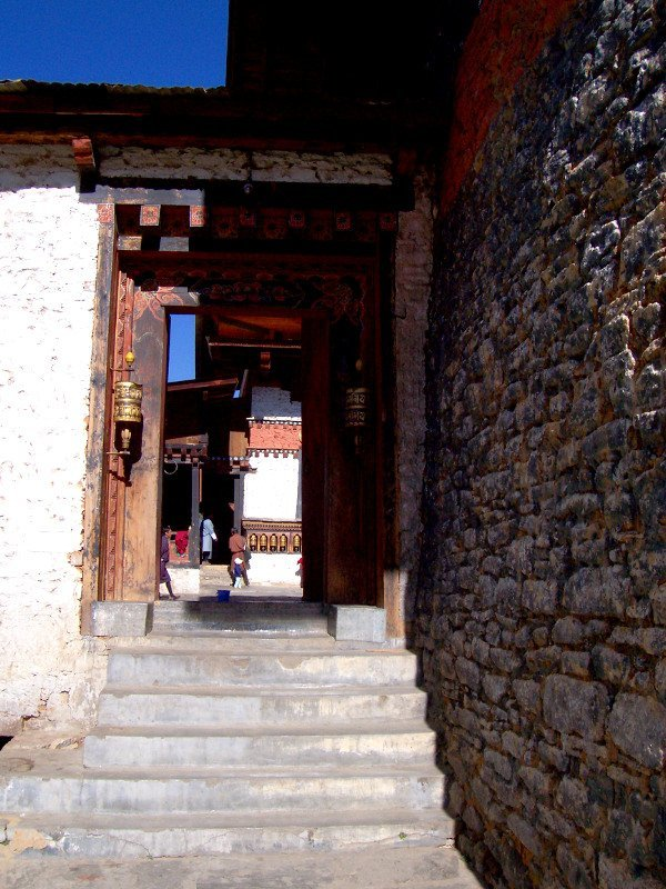 From the courtyard of one of the Best Places To Visit In Thimphu Bhutan, an ancient temple named Changangkha Lhakhang, a side door to the main courtyard
