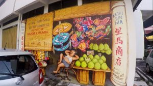 Things To Do In Ipoh - Mural Art of a Provision Store filled with fruits, lanterns, and the store owner
