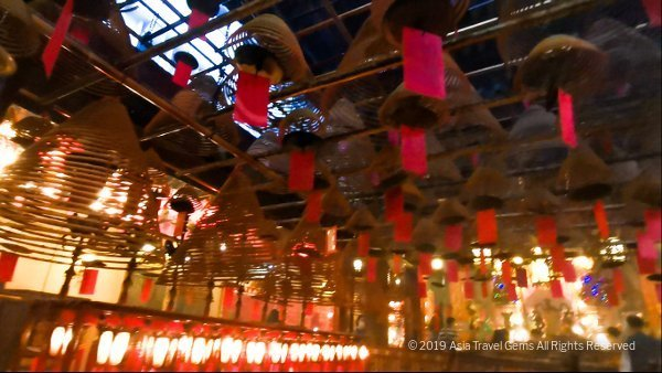 Incense Coils hang above with prayers and wishes from devotees
